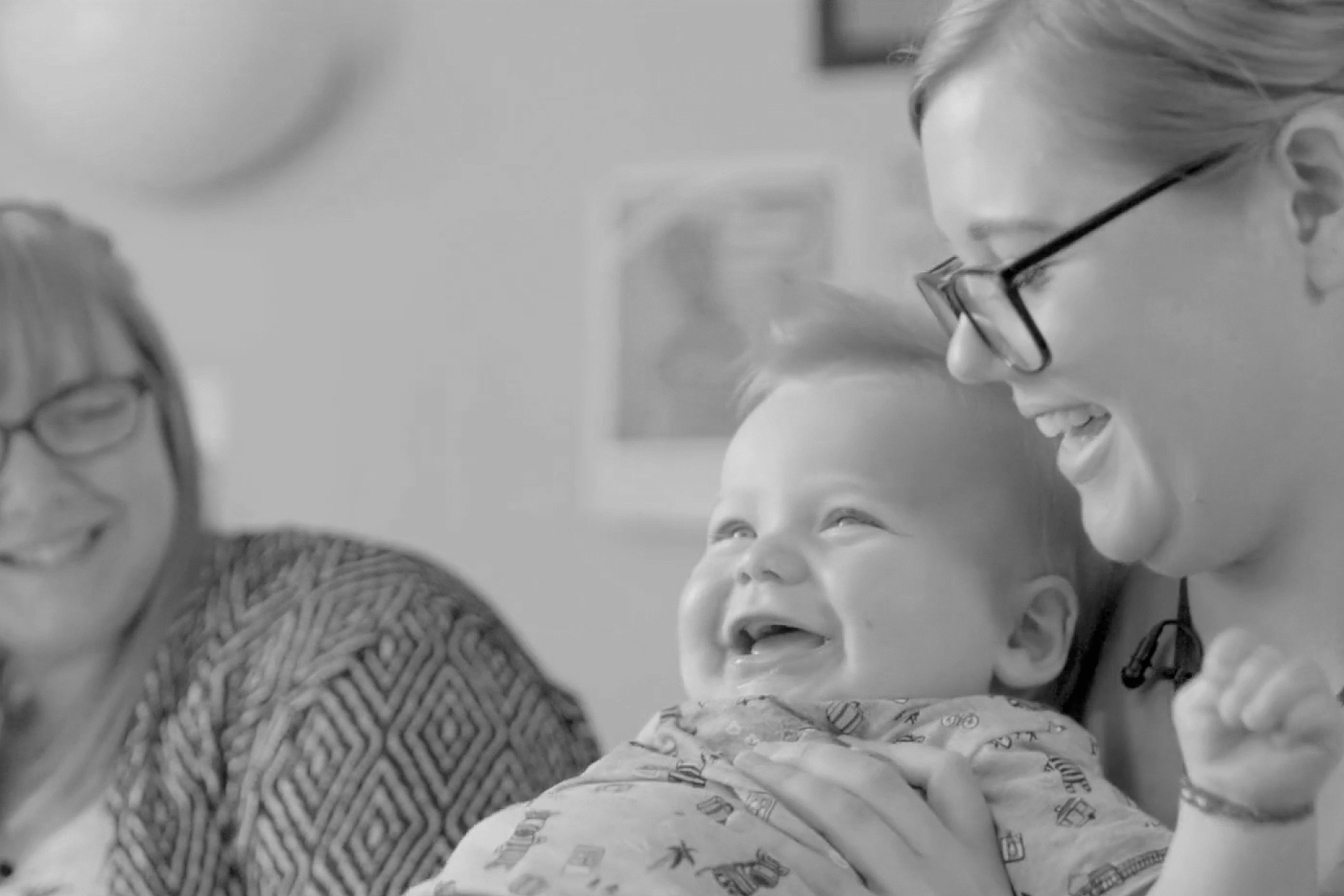 Baby laughing with parent and nurse
